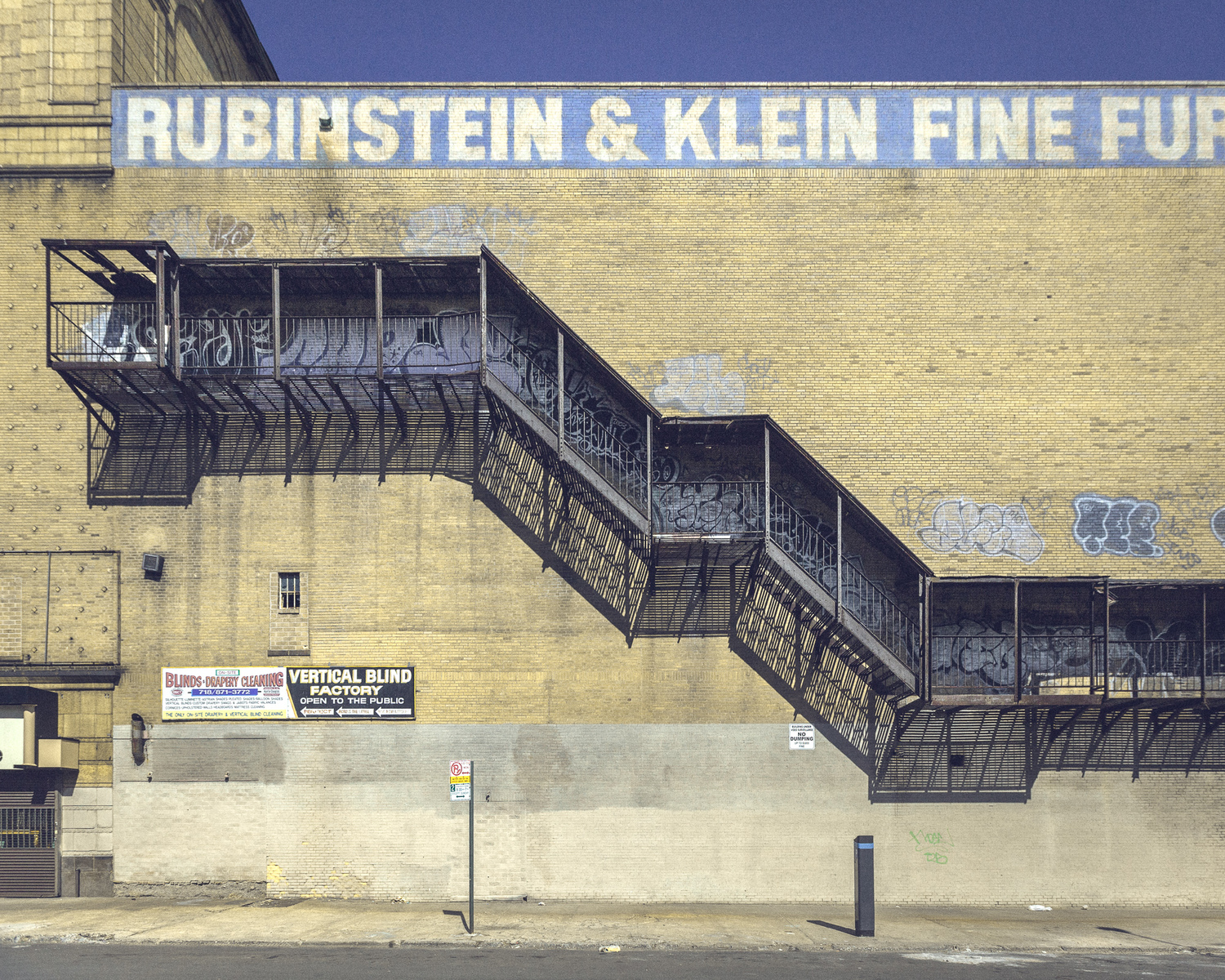 A fire escape like this one on a windowless structure is a sure sign that a building was once a movie theater.