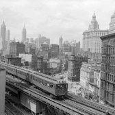 The Third Avenue elevated train rumbles across lower Manhattan, early 1900's.