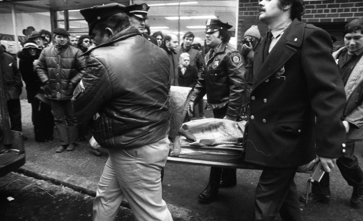 1970's: A body is covered and carried away after a patrolman was killed during a shooting at the 8th St. subway station in 1975.