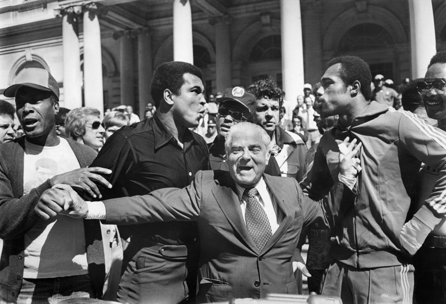 """Sept. 13, 1976: Feathers ruffled, chests puffed out, Muhammad Ali, left, and Ken Norton, right, talked tough for the benefit of the media on the steps of City Hall (photo Page 47 of this paper). Fortunately, Mayor Beame was on hand to keep the peace. The peace ended, according to schedule, on Sept. 28 when Ali beat Norton and retained the world heavyweight championship, though not without controversy. """"I thought I won it,"""" Norton said later. """"Ali knew I won it. The people knew I won it."""""""