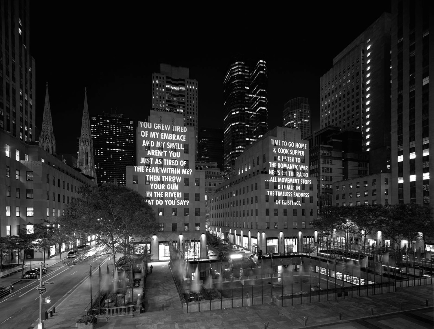"Rockefeller Center lit up by Holzer's projections in 2005. The words on the left are an excerpt from the poem ""He Embraces His Murder"" by Mahmoud Darwish. The words on the right are an excerpt from the poem ""My Sad Self"" by Allen Ginsberg."