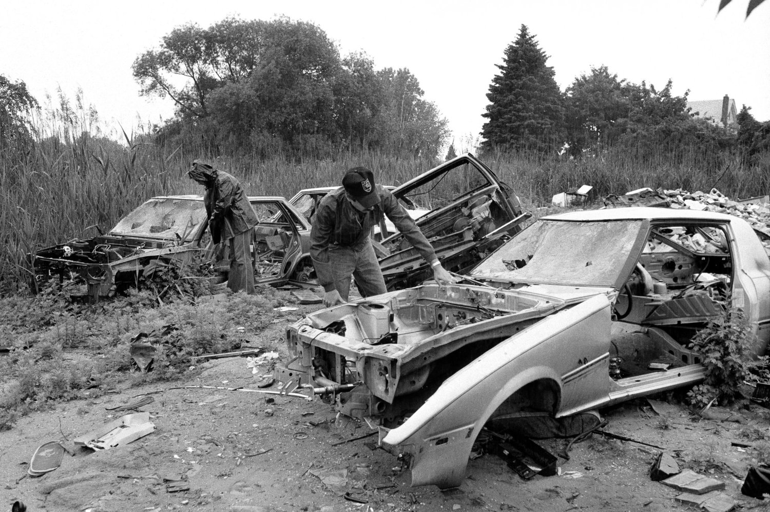 Police officers viewing abandoned cars on the Queens-Nassau border. June 5, 1985.