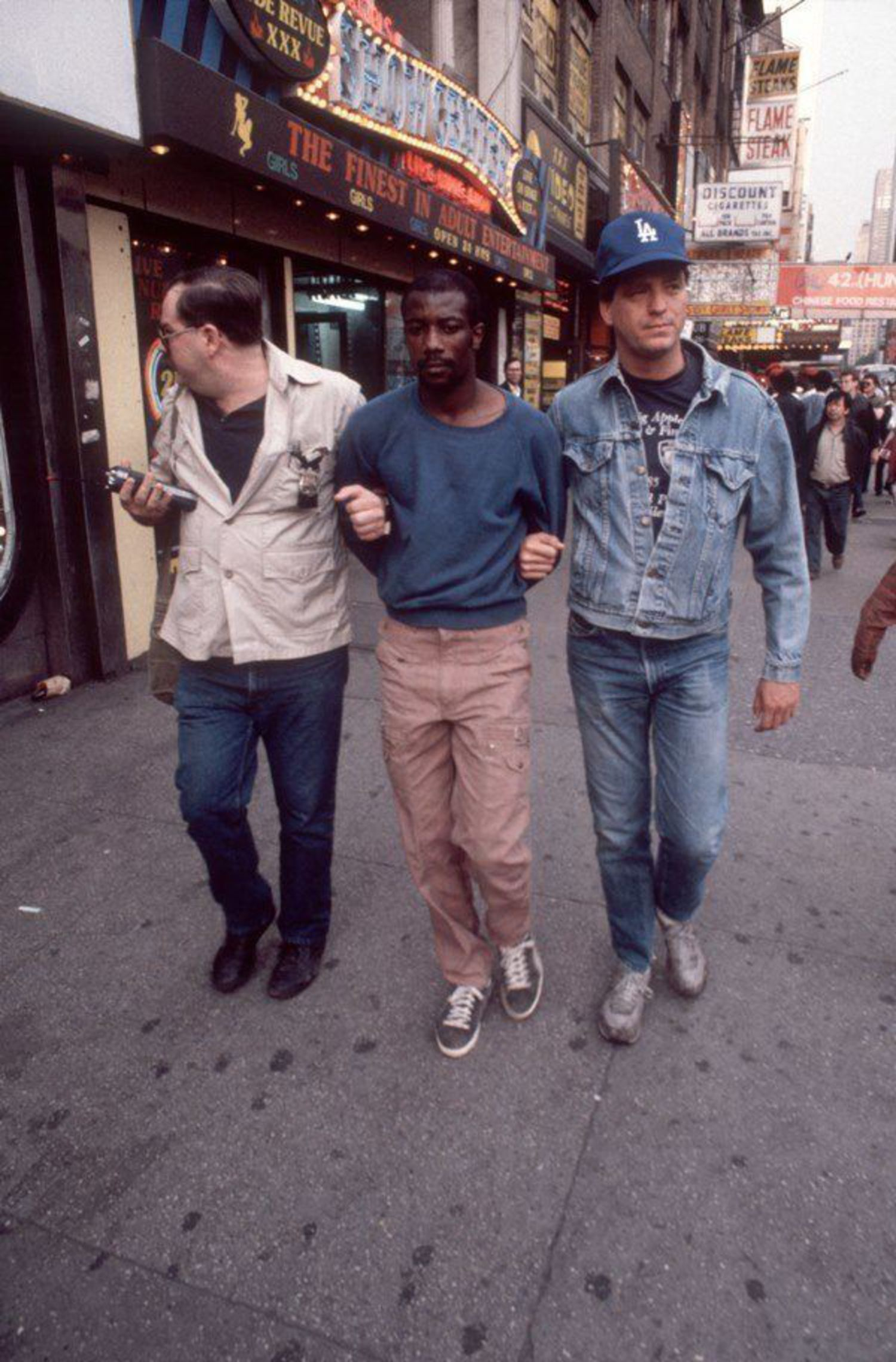 Sex wasn't the only trade of Times Square: the rise of crack-cocaine and the ability to operate on the street made the area a haven for drugs. In the above photograph, an undercover cop leads a man who's been arrested for selling crack in 1986.