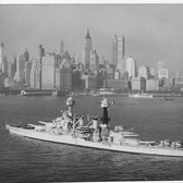 The battleship Colorado (BB 45) steams off New York City with the city's historic skyline serving as a backdrop.