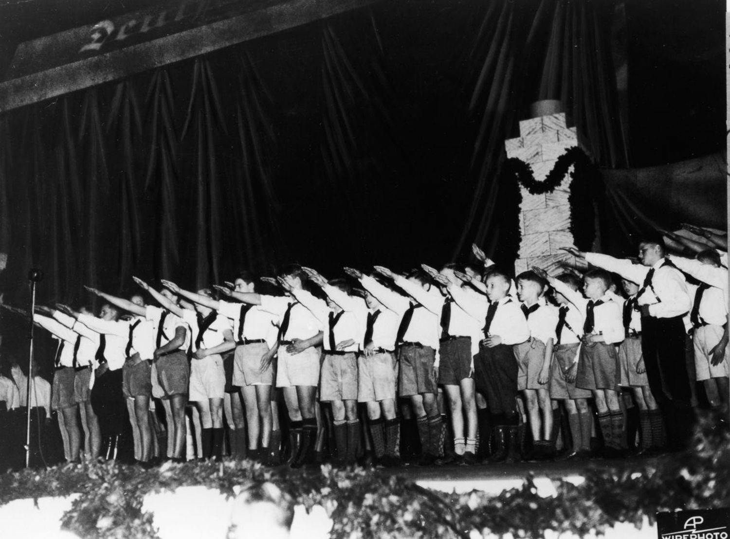 Boys in uniform salute during a pro-Nazi rally.