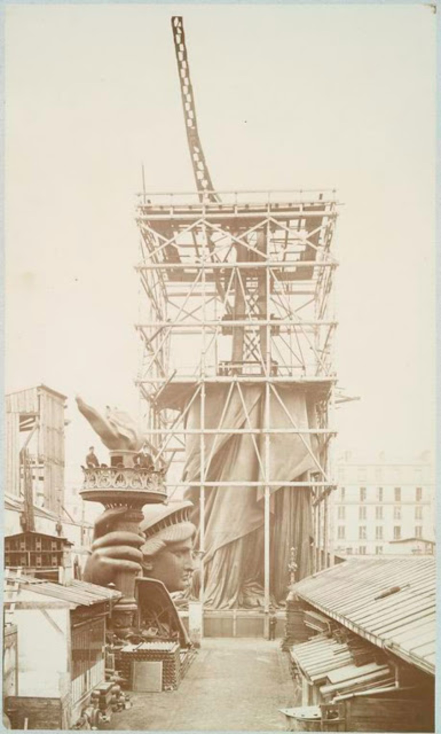 Assemblage of the Statue of Liberty in Paris, showing the bottom half of the statue erect under scaffolding, the head and torch at its feet, 1883.