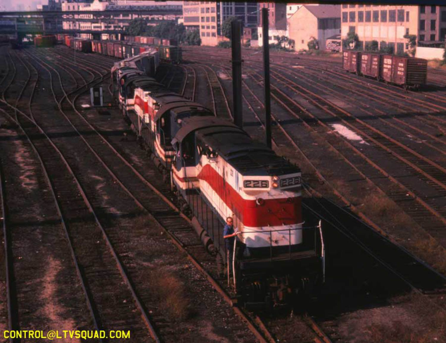 "This is a 1982 photo of a long inbound freight LIRR freight train arriving in 'Yard A' at sunnyside, as seen from the Honeywell Avenue bridge. You can see the 7 train and CN West factory in the distance. The train is being lead by 4 ""C420"" freight locomotives built by the American Locomotive Company, located in upstate NY – they're still painted in a red white & blue paint job applied to many LIRR locomotives in celebration of the 1976 US bicentennial."