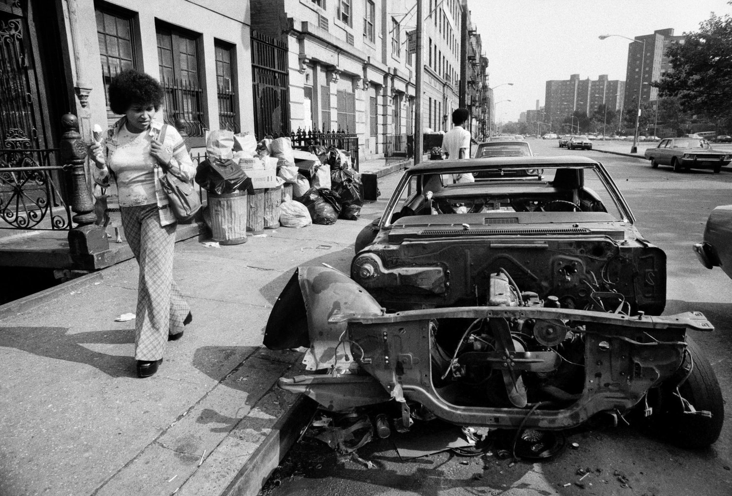 A pedestrian looking at a stripped car in the East Village on Oct. 14, 1979.