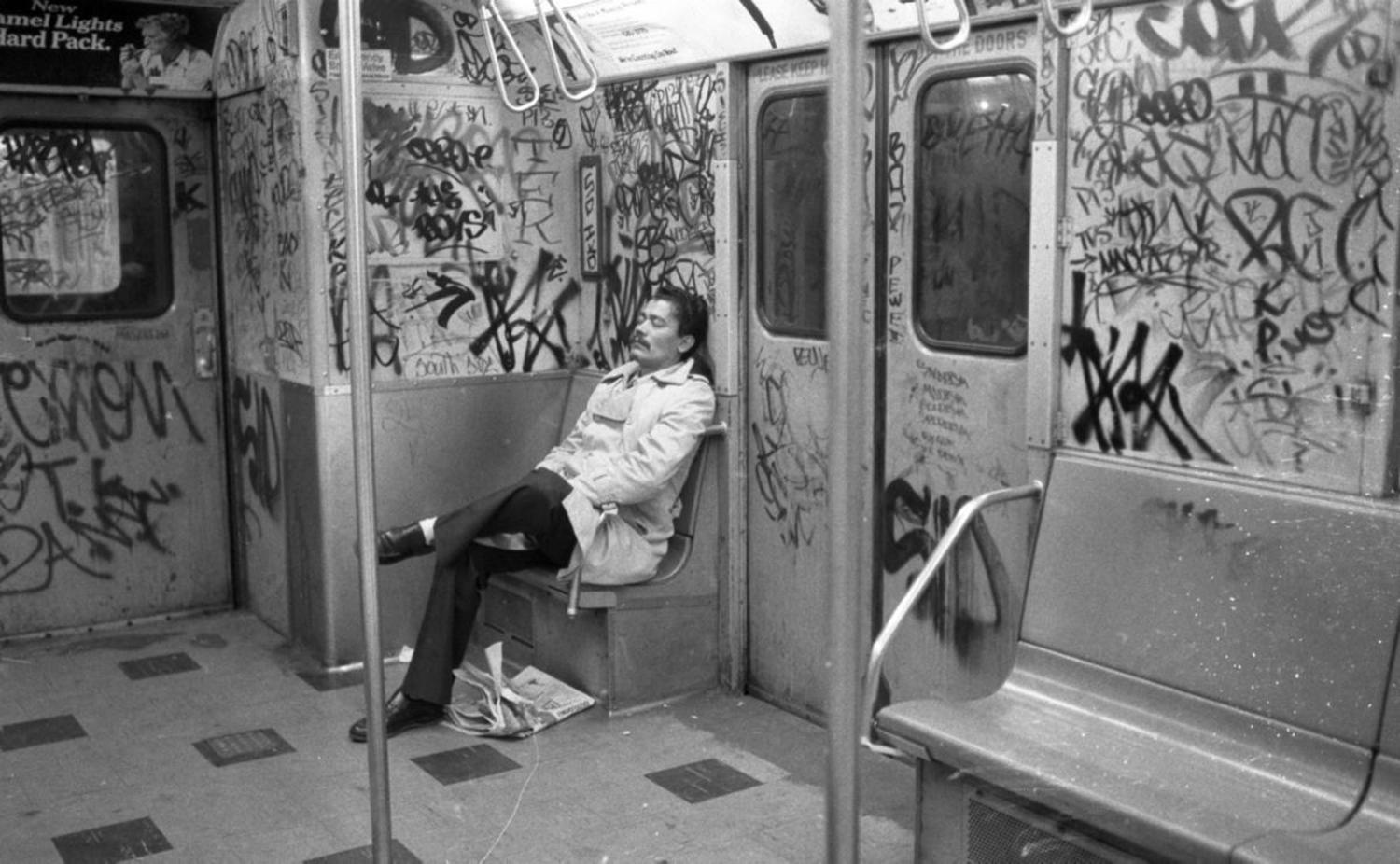 1980's: The writing's on the wall: A tired passenger rests while seated in an empty, graffiti-filled subway car in 1980.