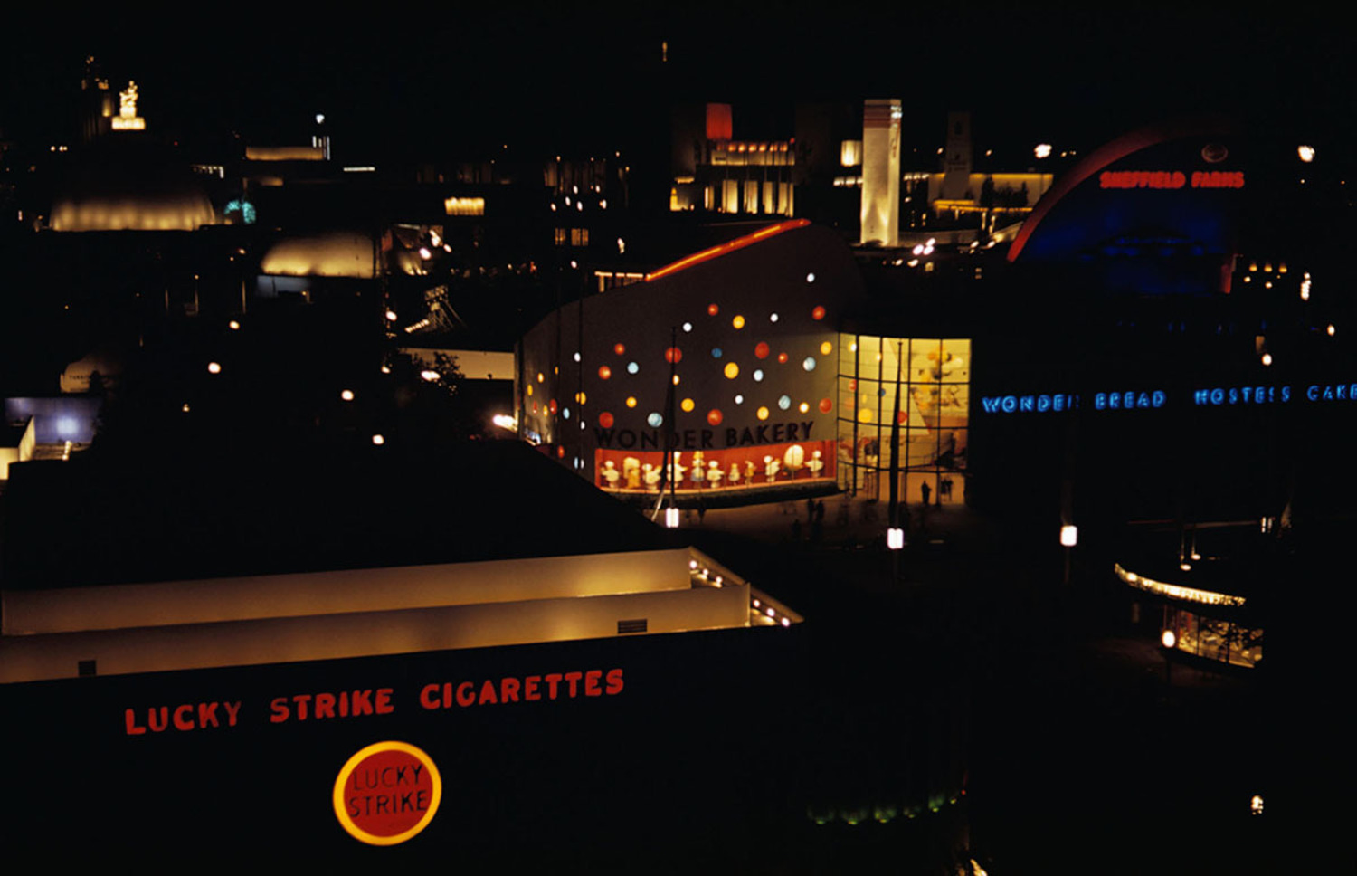 The Lucky Strike Cigarettes and Wonder Bread Bakery buildings are shown illuminated at night at the 1939 New York World's Fair.