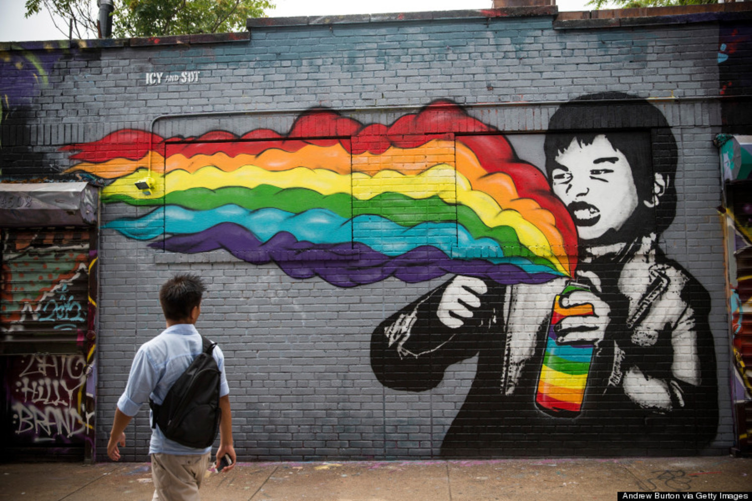 A man walks past a mural painted on the '5 Pointz' building on August 9, 2013 in the Long Island City neighborhood of the Queens borough of New York City.