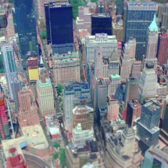 The video chronicles a day in New York City, beginning with an aerial shot depicting Lower Manhattan skyscrapers. 50 West by Time Equities, JAHN and SLCE Architects is visible at the bottom left. The two footprints where the Twin Towers at the World Trade Center stood are evident just north of this residential tower.