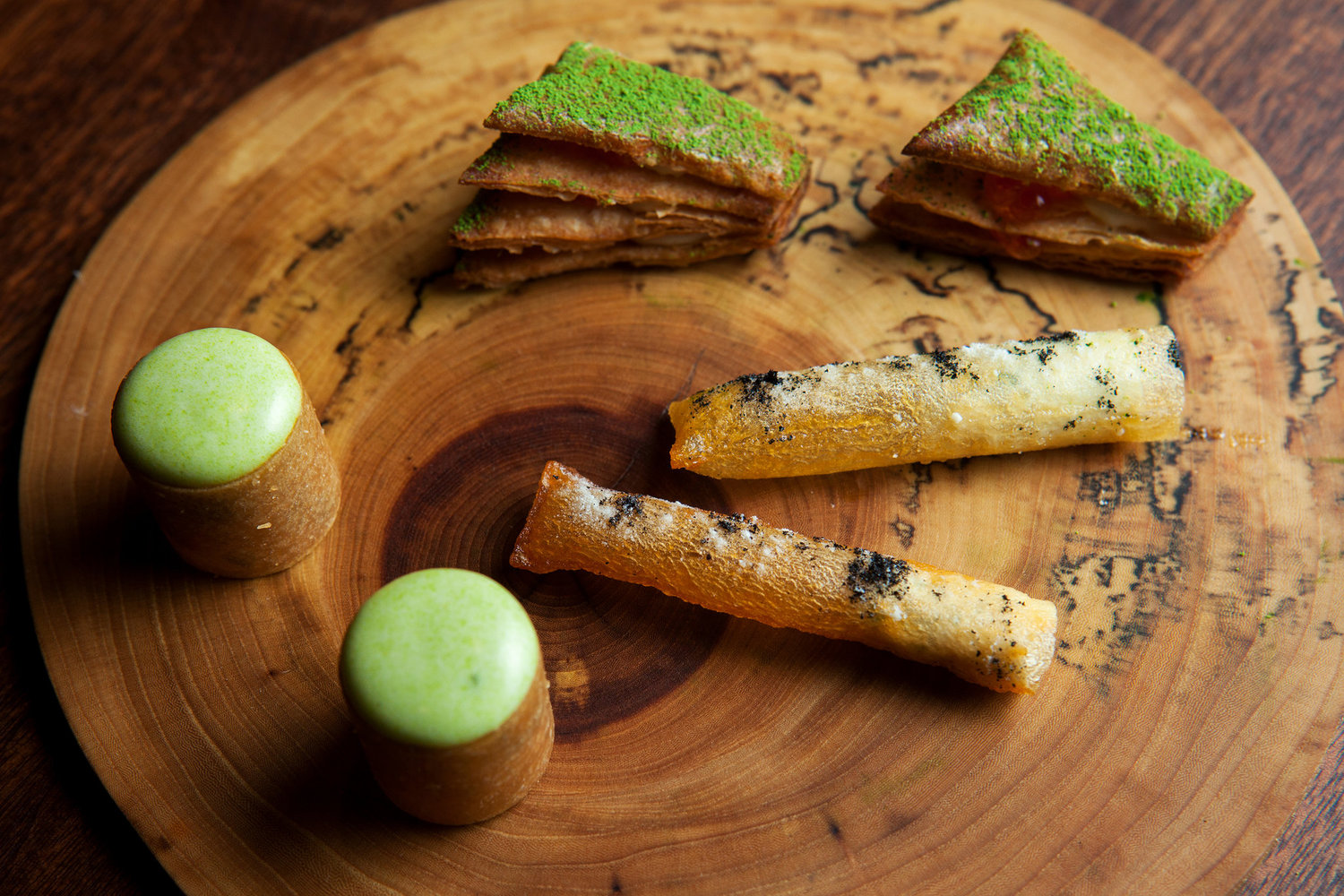 Momofuku Ko moved to an alleyway off East First Street earlier this year. One-bite mille-feuille, whose crisp layers of rye pastry sprinkled with green tea powder hold lush béchamel and briny little globes of trout roe, are shown with pommes soufflé and lobster paloise.