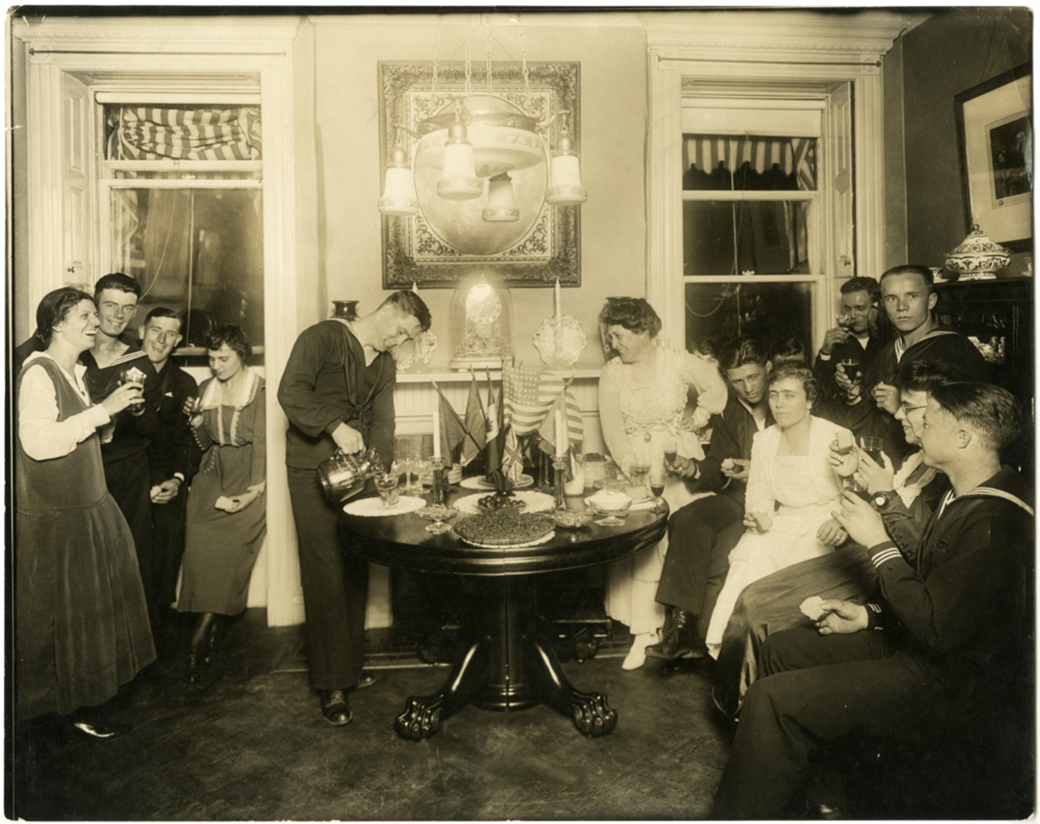 Alice Foote MacDougal entertaining a group of sailors in her small apartment, circa 1917-1918; photograph by Jessie Tarbox Beals.