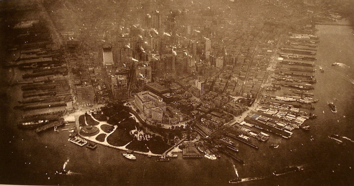 The lower end of Manhattan Island photographed from a height of about 800 feet.  Battery Park with the elevated railroad winding through it occupies most of the lower portion of the picture' the small park slightly above it is Bowling Green with the new Custom House facing it.  The little dark spot to the right is Corlears Hook Park.  The blurs around the corners of the pictures are due to the action of the salt water when the plates fell into Long Island Sound