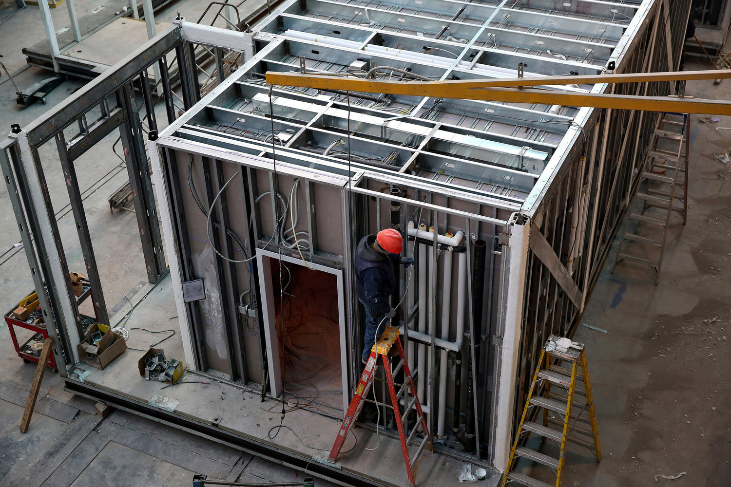 Plumbing is installed into open exterior walls. Open walls allow this type of work to be done at the same time as interior finish work.