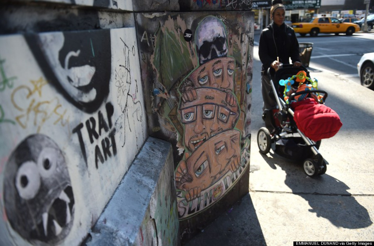 People walk by street graffti in New York on April 25, 2014.