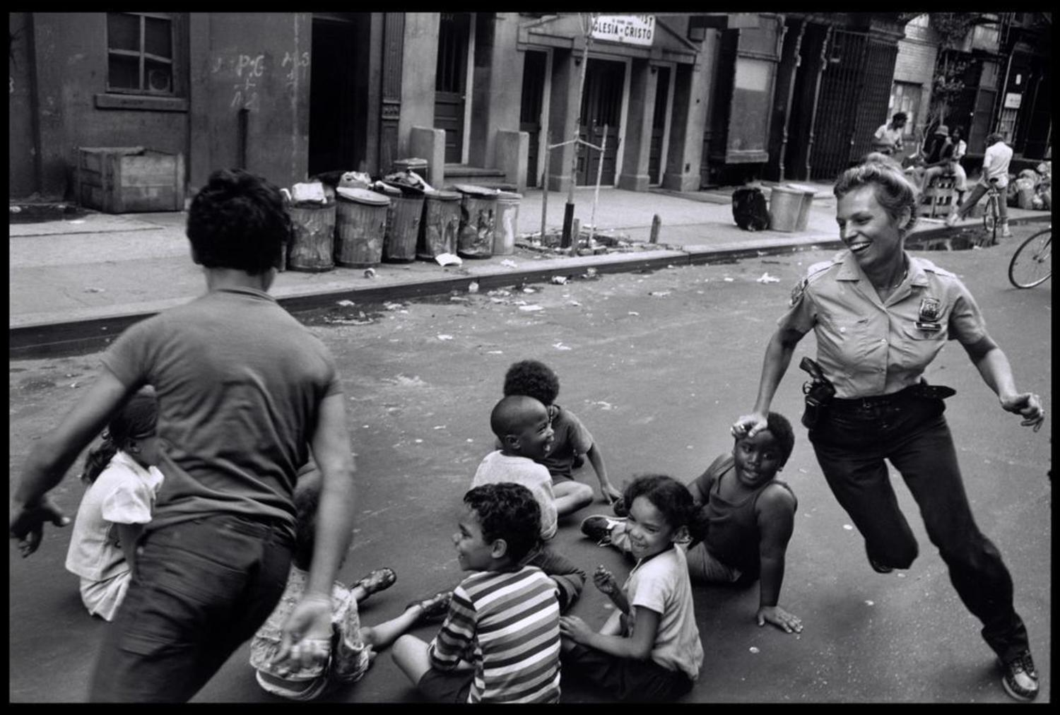 A police woman plays duck duck goose with children in Harlem, NYC, New York, US in 1978.