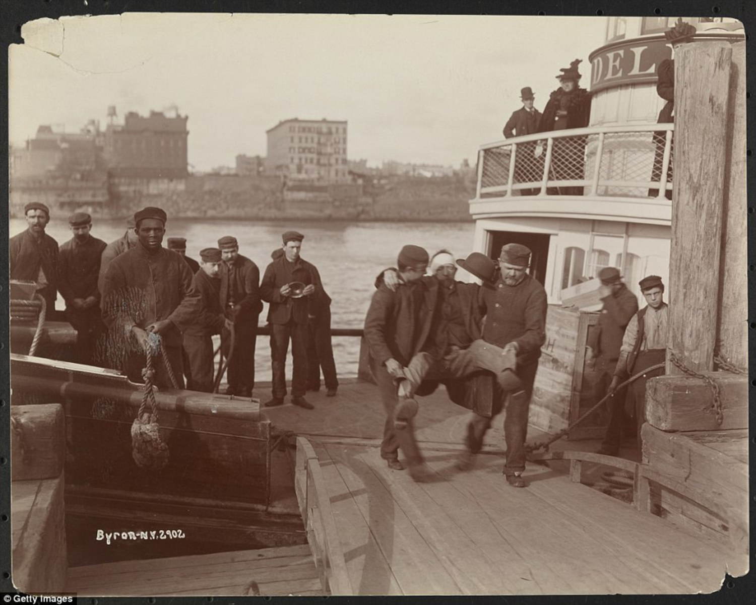 Two men carrying a patient from the ferry to the pier on Welfare Island, New York, New York, mid 1890s