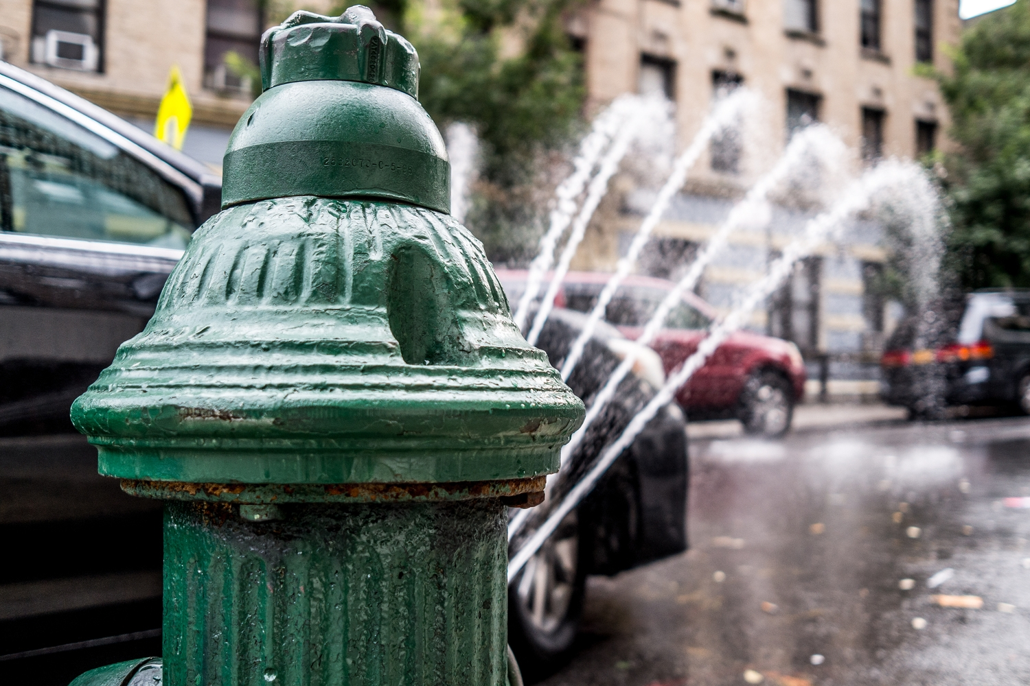 Classic NYC Summer | An open hydrant spraying water on a hot summer day.