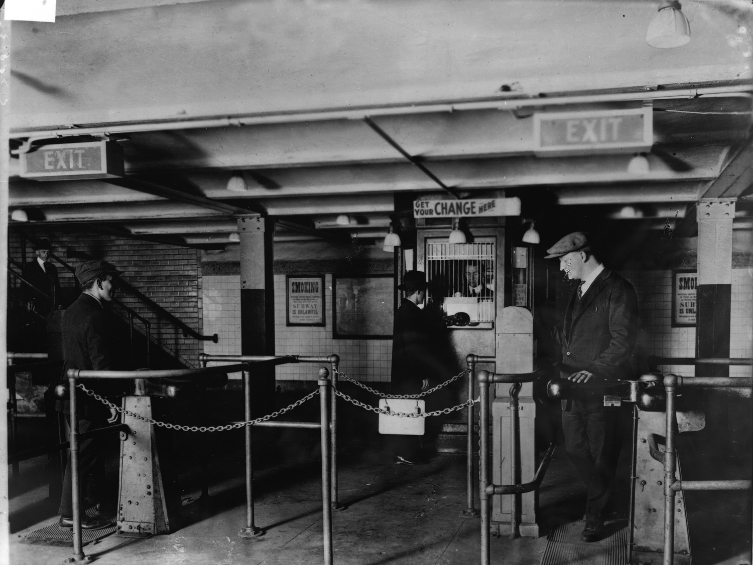 A man gets change in nickels from a change booth operator so he can pass through the new nickel-operated turnstiles which have replaced the ticket and ticket-chopper (a man who manually cut tickets at the gate) system in the New York City subway, early 1920s. The move allowed subway companies to reduce operating costs by drastically reducing personnel.