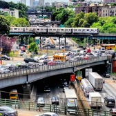 From the days before social distancing, a 4 train runs over the Cross Bronx Expressway
