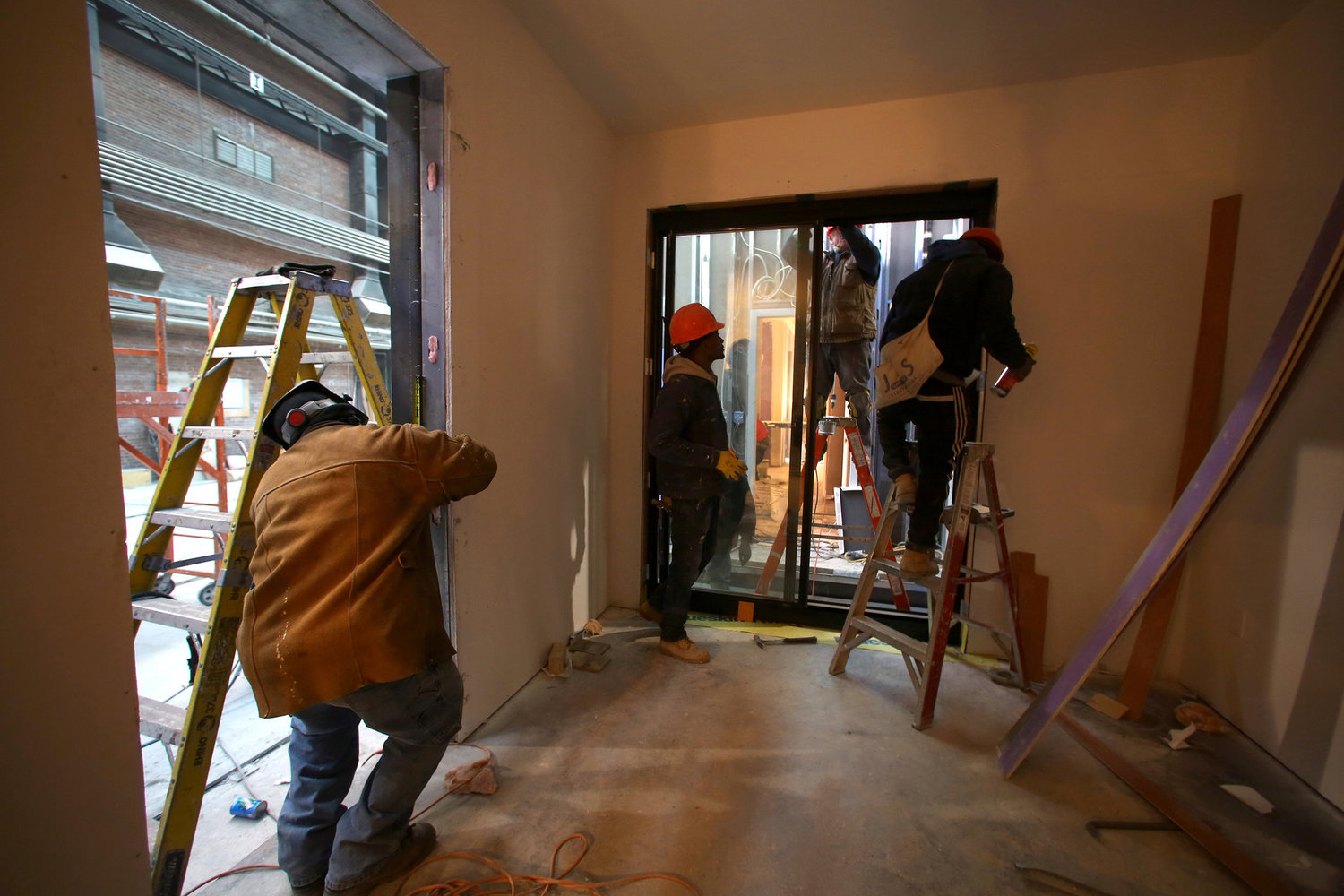 Workers installing a sliding window in the main living area of an apartment.