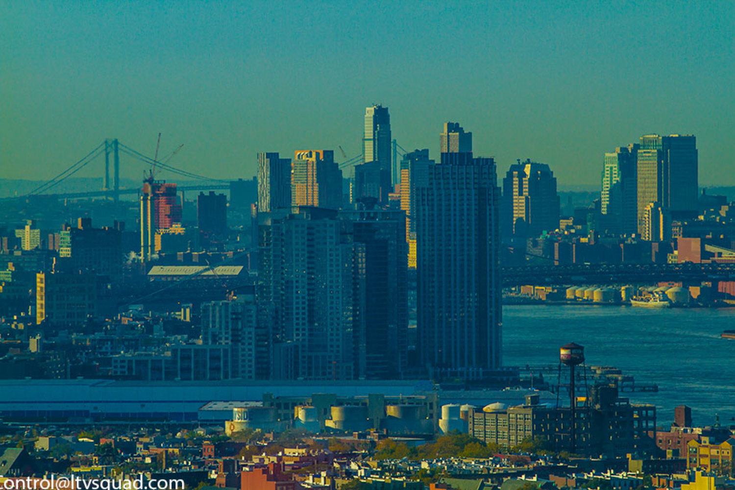 Williamsburg, and Lower Manhattan. The watertower at Greenpoint Terminal is in the foreground.