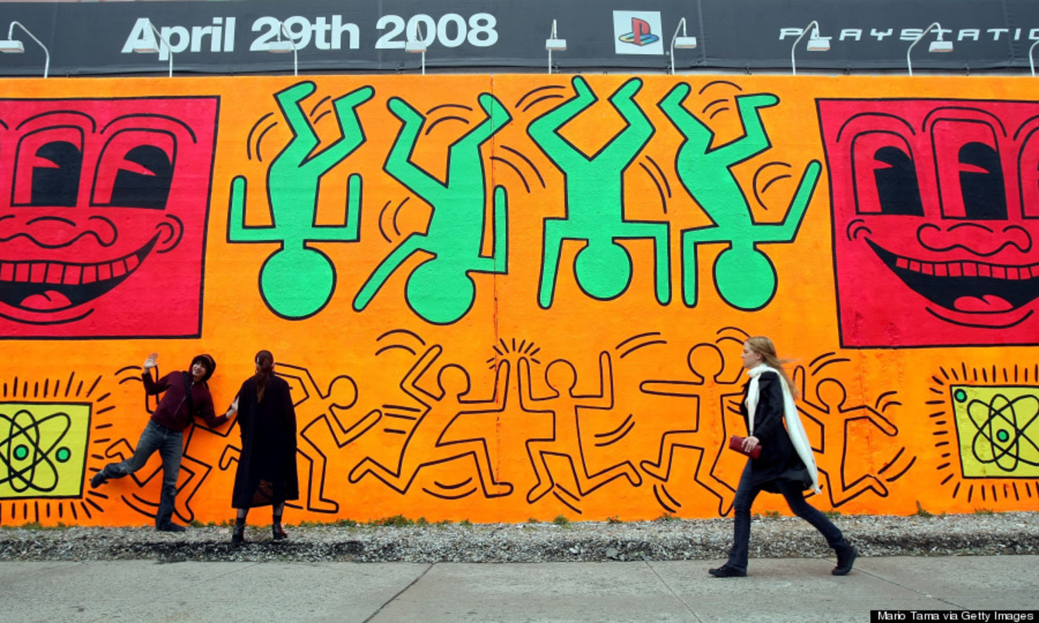 People walk by a re-creation of an untitled mural painted by artist Keith Haring on the corner of Houston Street and Bowery in Manhattan May 2, 2008 in New York City.