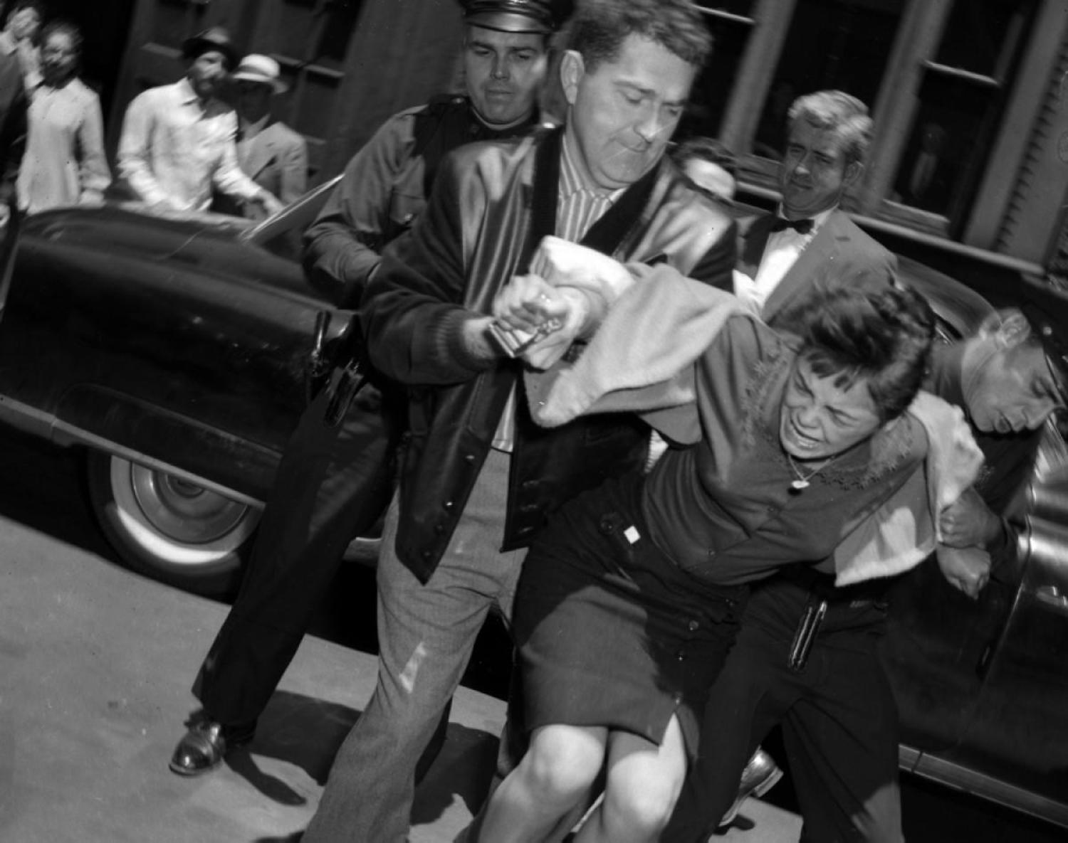 Mob Moll, 1959: They start them young! While most people consider the mob to be made up of a bunch of men, that acutally isn't the case. Here, 15-year-old moll Carmen Martinez doesn't go down without a fight as she is hauled off by police to Felony Court for the murder of 17-year-old Raul Banuchi.