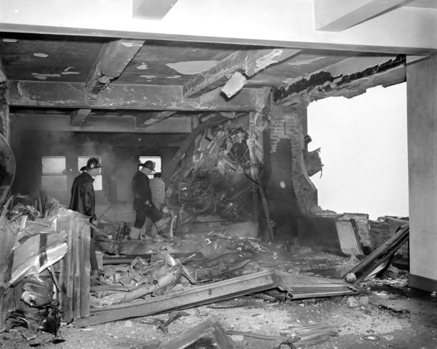 B-25 Mitchell bomber smashed beyond recognition into Empire State Building. This is a picture of the wreckage-strewn 79th floor where the bomber tore a 18-foot hole in wall. Propeller is embeded in the wall at the left.