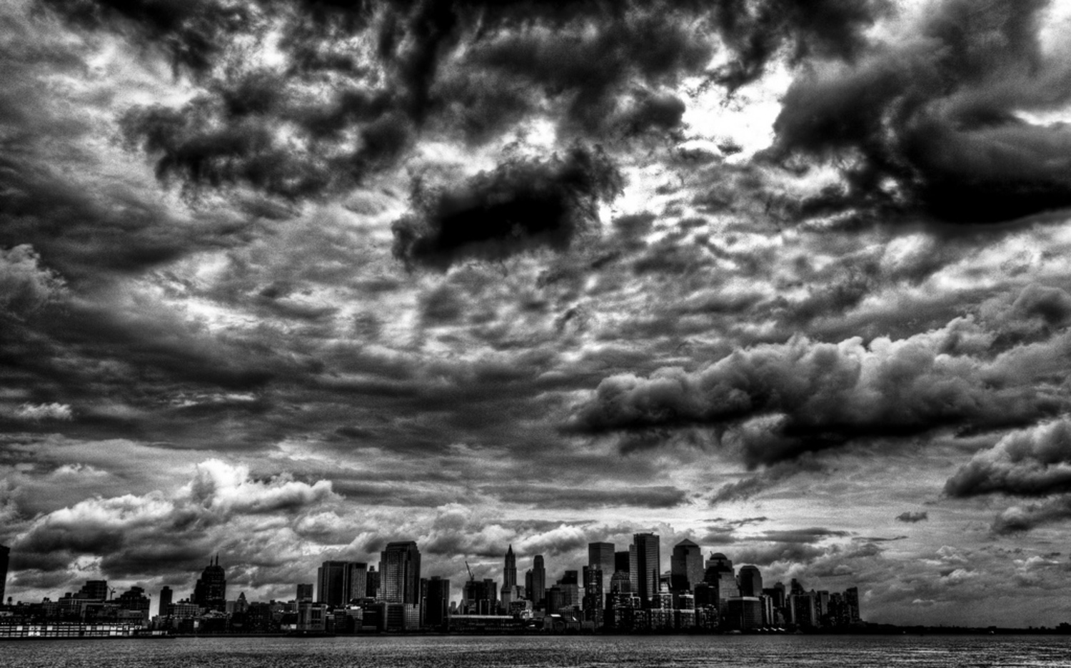 "Stormy Gotham | Storm clouds over Lower Manhattan. Taken from Hoboken, NJ. 3 Exposures, +2 EV, 0 EV, -2 EV lighting was tweaked in LightRoom, Photoshop was not used.   <a href=""http://www.bighugelabs.com/onblack.php?id=3656101668&size=large"" rel=""nofollow"">View Large On Black</a>"