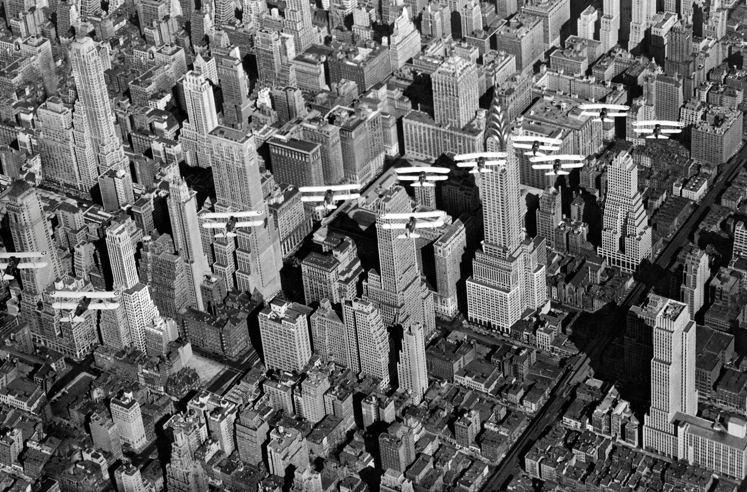 United States Army Air Corp biplanes flying in formation over Midtown Manhattan and the recently completed Chrysler Building. Circa early 1930s.