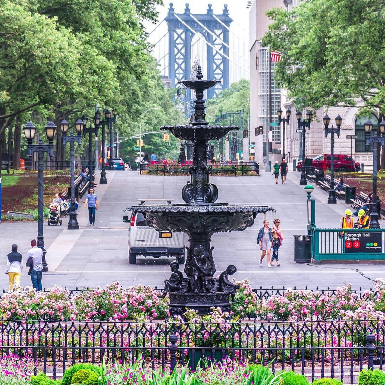 Columbus Park in downtown Brooklyn. Named after Christopher Columbus, the park is one of the the city's first major urban parks that continues to be a gathering place for people of different cultures and ages, and hosts a wide variety of events and assemblies. Behind the fountain is part of the Manhattan Bridge. Downtown Brooklyn, New York City.