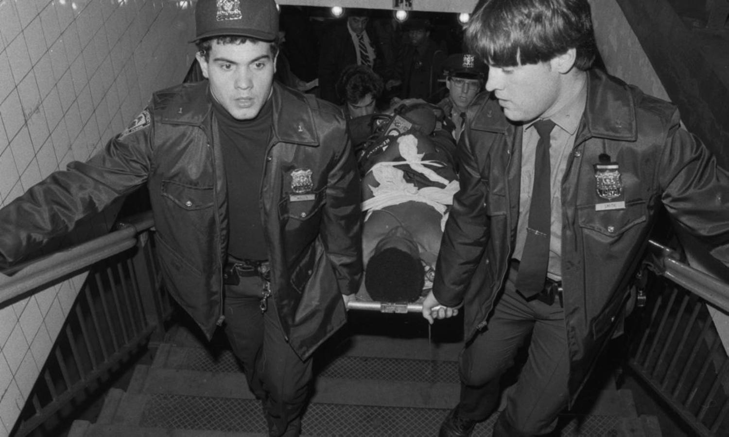 1980's: One of Bernhard Goetz's gunshot victims is carried out of the subway by paramedics.