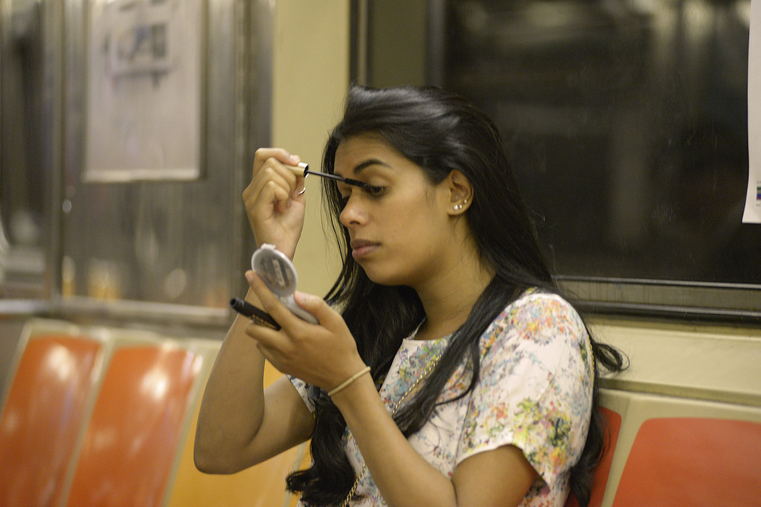 Woman Applying Mascara on Subway