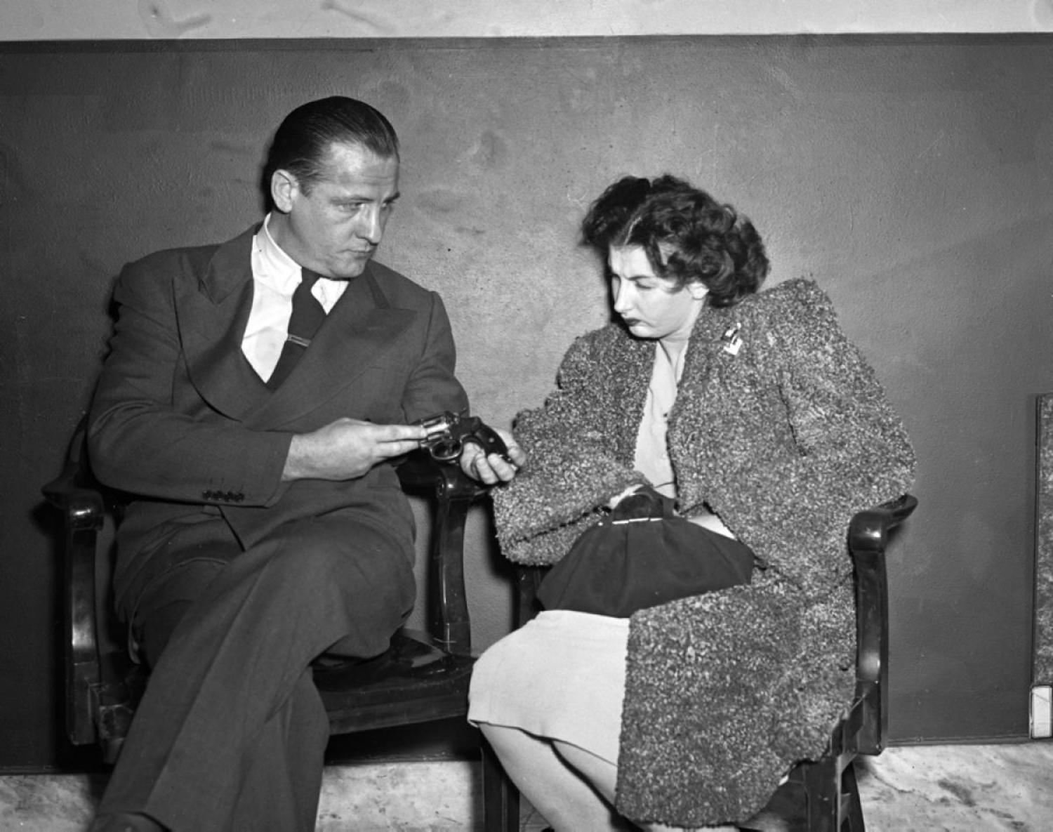 Mob Moll, 1947: Guns are apparently not a suitable purse accessory! Here, Lillian Stang, 23, is questioned by assistant DA James McGrattan after she was caught packing heat in 1947.