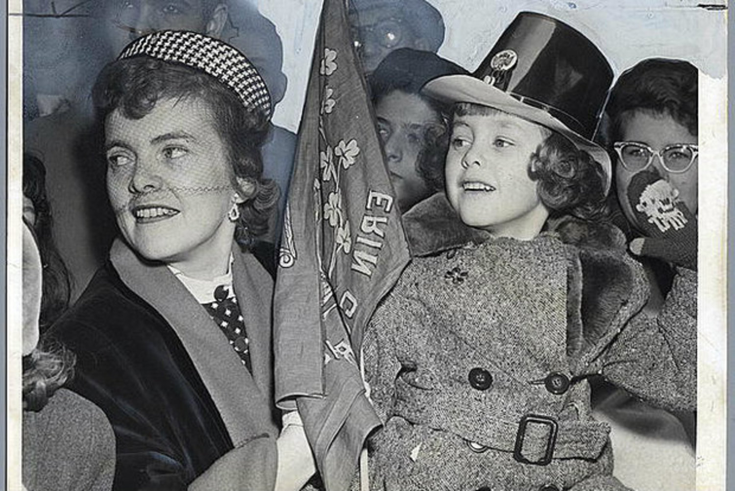 A mother and daughter pair cheer on St. Patrick's Day revelers near 49th Street in 1953.