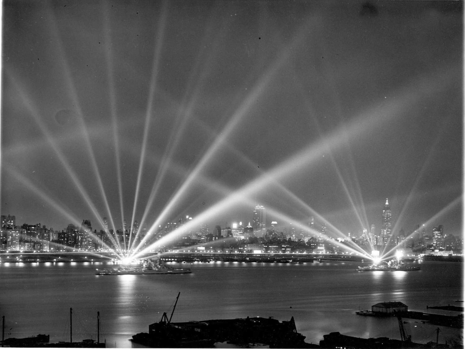 Battleships USS Texas and USS New York on the Hudson light up the night sky with their huge searchlights in search of imaginary aerial attackers. New York, 3 May 1939.