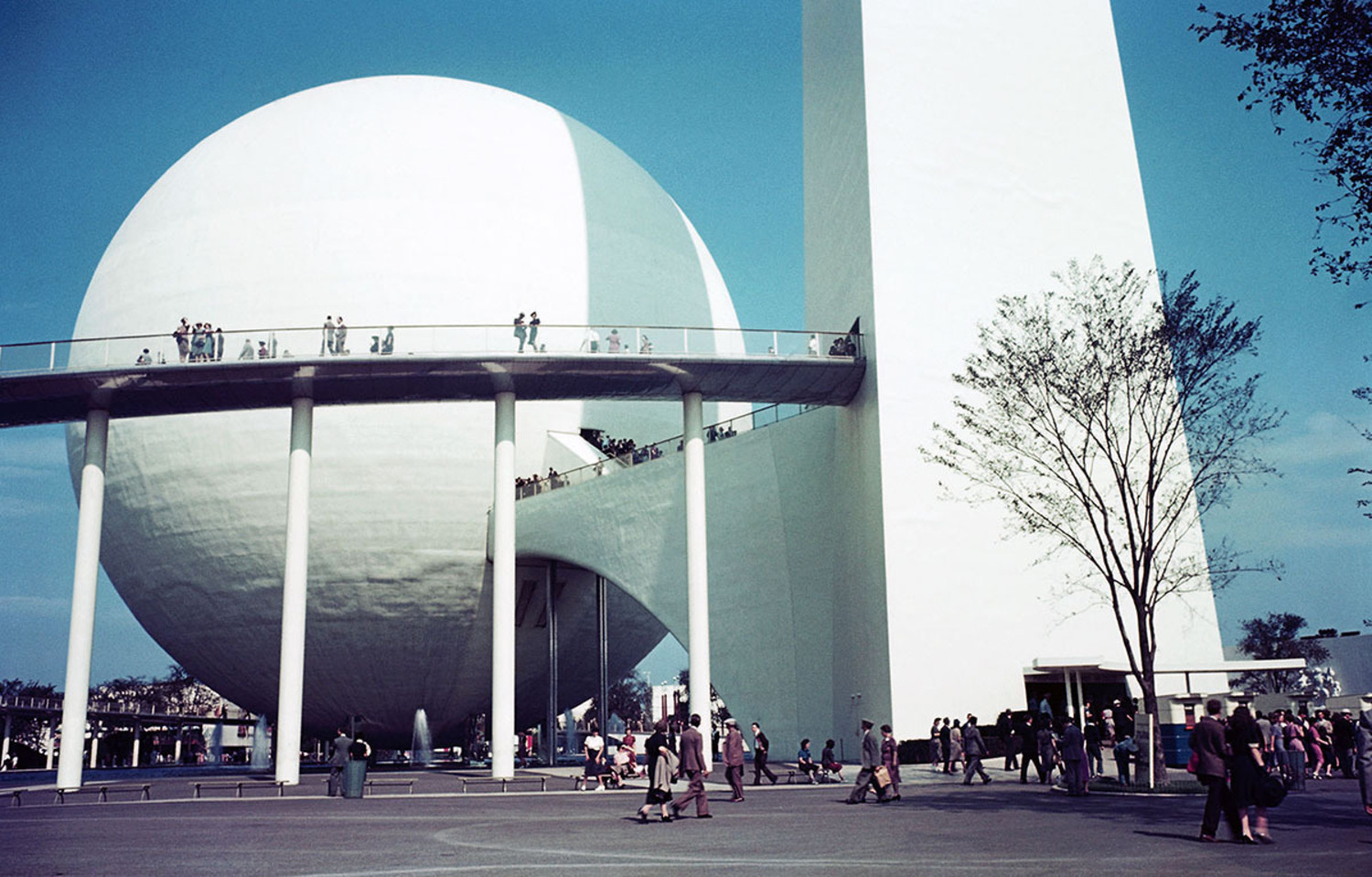 People visit the Trylon and Perisphere at the 1939 New York World's Fair. Inside the Perisphere was a diorama of a futuristic utopian city named Democracity. After viewing, visitors would leave by descending a long spiral walkway named the Helicline.