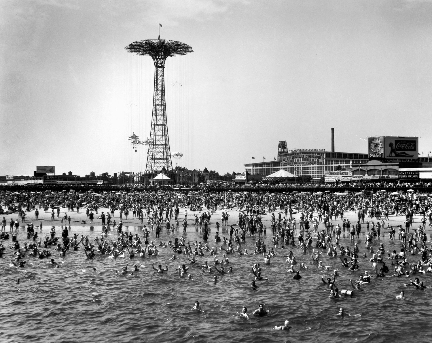 The beach at Coney Island. The parachute ride is visible in the background, 1952.
