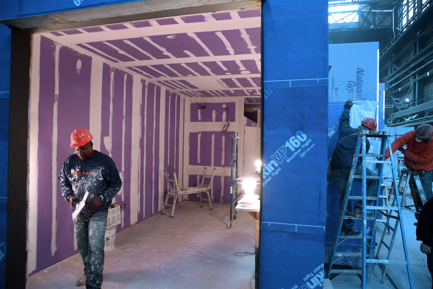 A look into the main living space of an apartment after drywall has been installed.