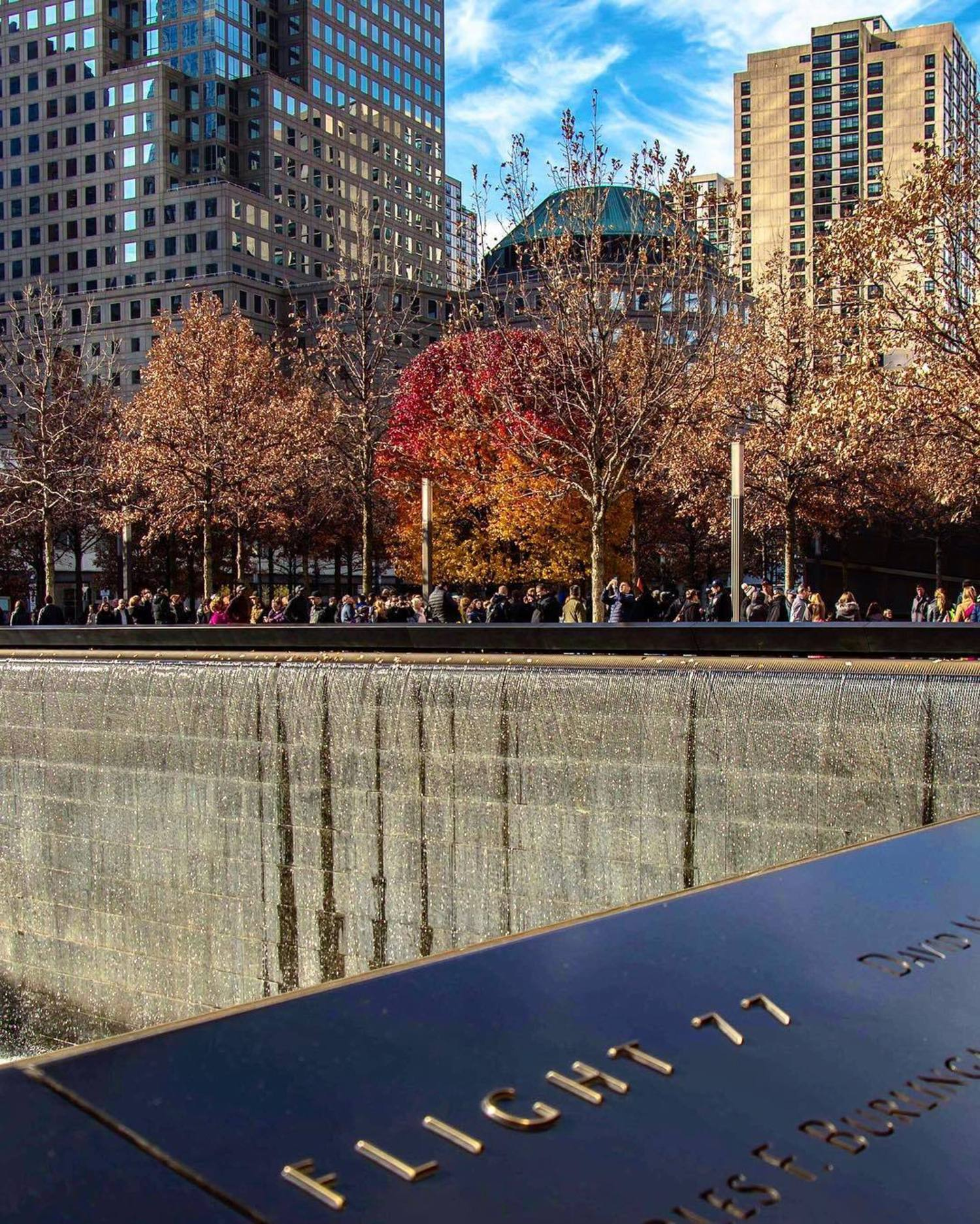 "The beautiful, inspiring Survivor Tree stands in it's Autumn glory ❤️🍁🍂 This is the waterfall where World Trade Center 2 once stood.  A Callery pear tree became known as the ""Survivor Tree"" after enduring the September 11, 2001 terror attacks at the World Trade Center. In October 2001, the tree was discovered at Ground Zero severely damaged, with snapped roots and burned and broken branches. The tree was removed from the rubble and placed in the care of the New York City Department of Parks and Recreation. After its recovery and rehabilitation, the tree was returned to the Memorial in 2010. New, smooth limbs extended from the gnarled stumps, creating a visible demarcation between the tree's past and present. Today, the tree stands as a living reminder of resilience, survival and rebirth."