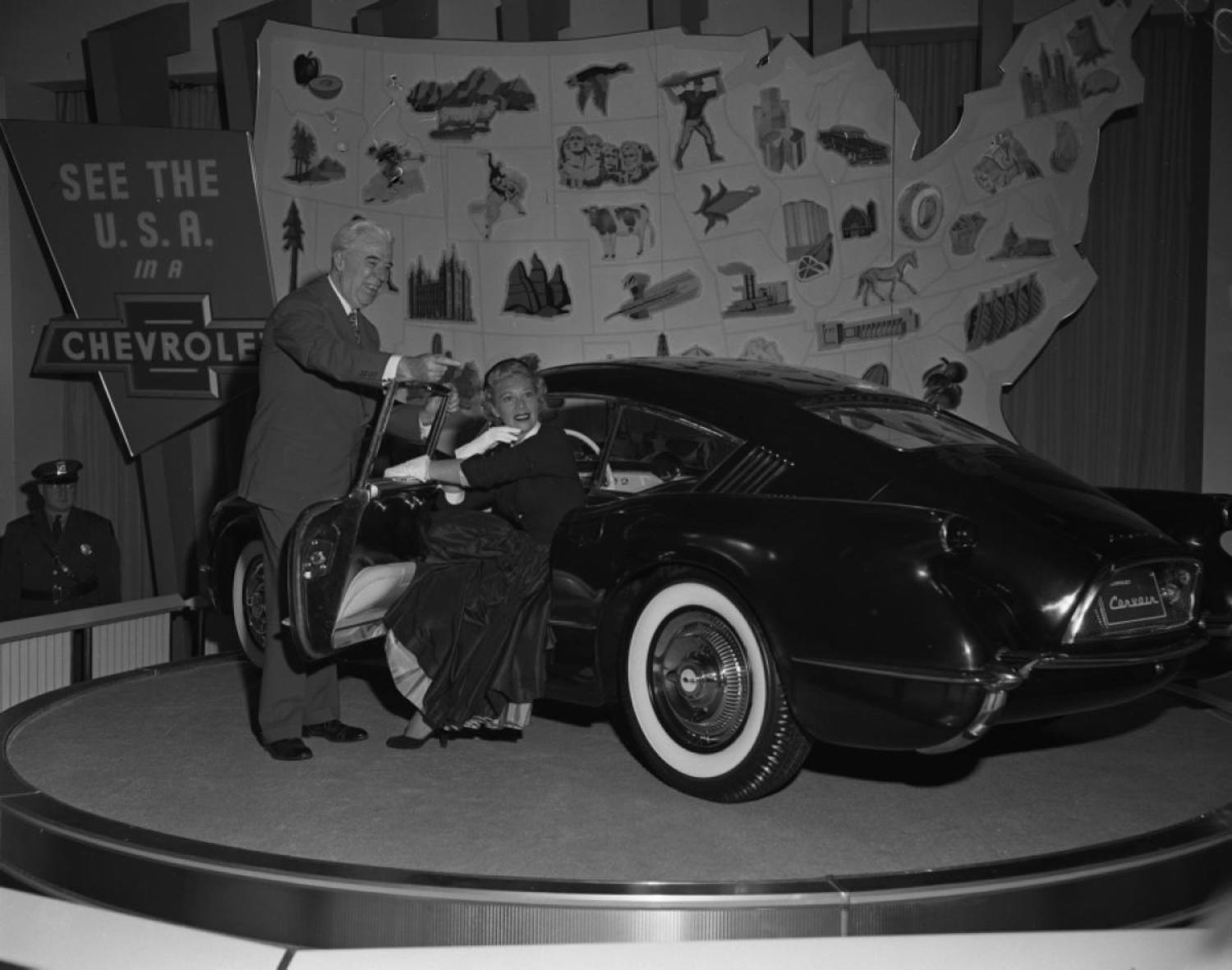 Singer Dinah Shore gets an up close look at the Chevrolet Corvair concept car at the General Motors Motorama exhibition held at the Waldorf.