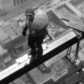 A construction worker on a beam high above the building at Wall Street, New York City, 1930.