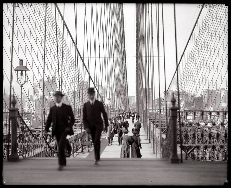 Dapper men and elegant women crossing Brooklyn Bridge, 1910