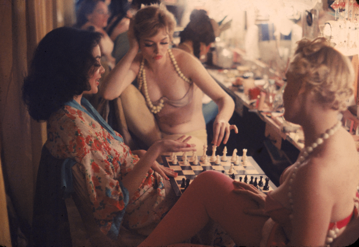 Between scenes in the show at New York's Latin Quarter, Pat Farrell prepares to make a chess move. Opponent (right) is Grace Sundstrom. Kibitzing at left is Shirley Forrest, an ex-schoolteacher.