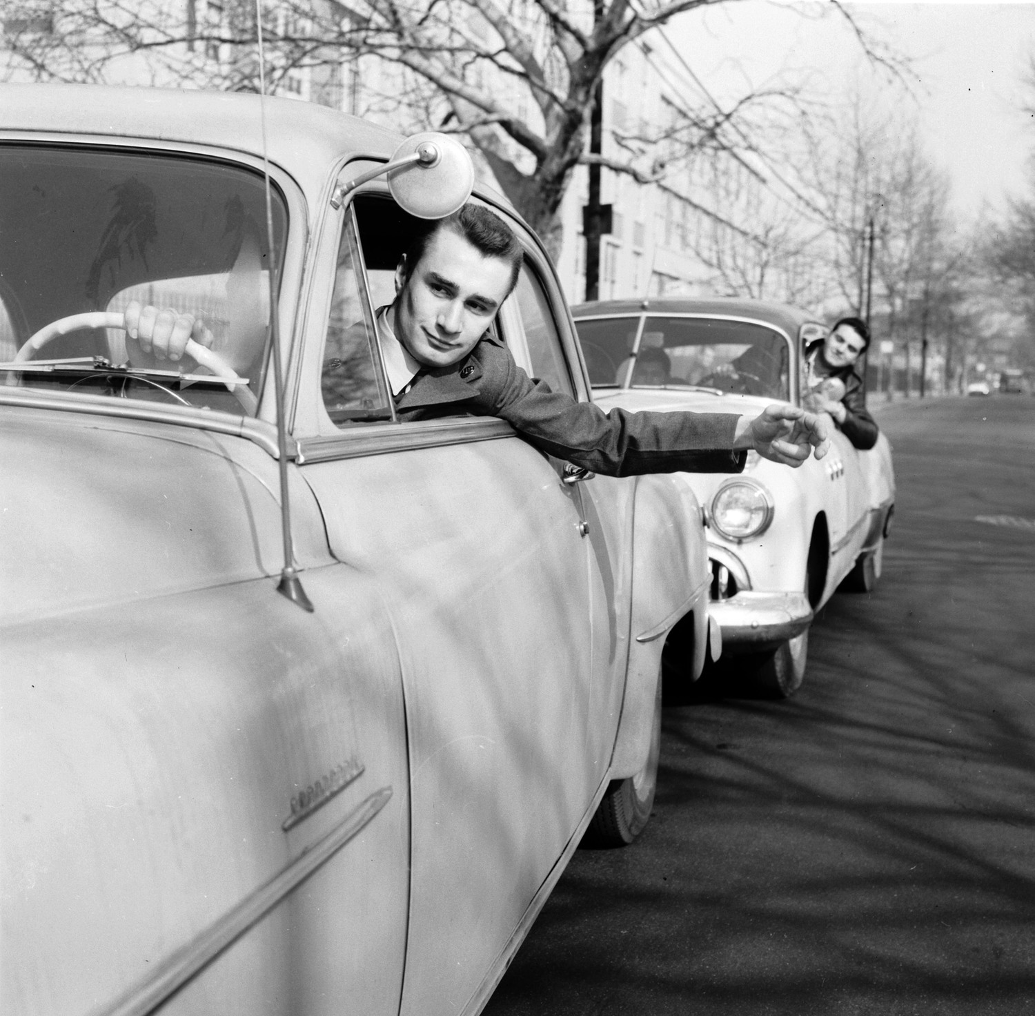 Students at Brooklyn School of Automotive Trades and members of the Automotive Custom Crafters Club are pledged to provide honest service to the motoring public without charge. Here they give a driver a push start, 1956.